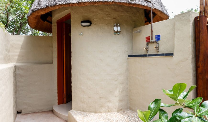 "Pangolin Hornbill  ""Bush Bathroom"" - consists of the outdoor shower and covered toilet and basin accessed by the private courtyard from the rondavel."