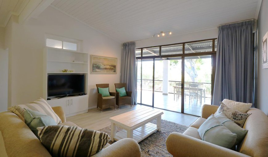 Oceana Beach house- Open plan lounge in contemporary beach house style, flat screen tv with DSTV, cosy couches and chairs.