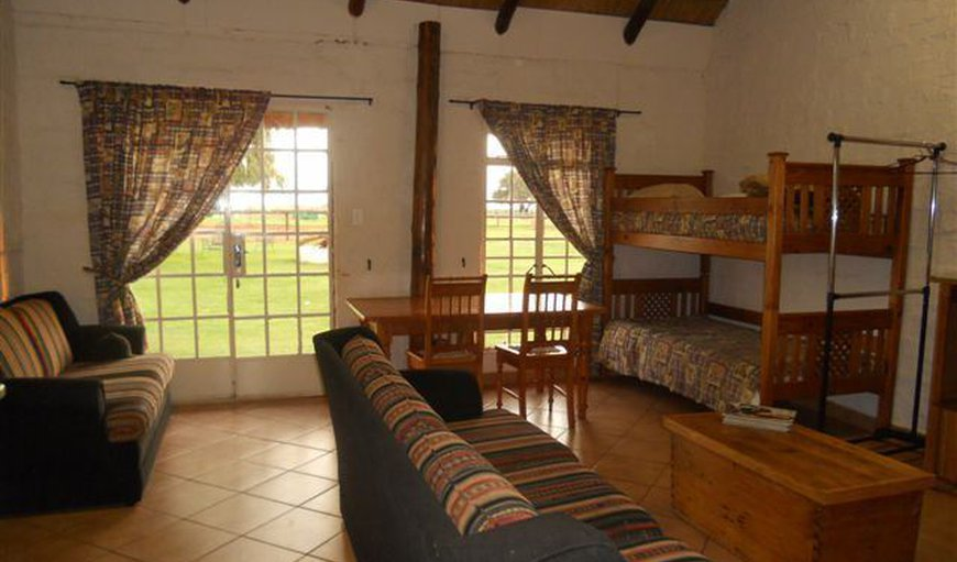 open plan room with now a double bed and 2 single beds.  bench for 5 th person in Lichtenburg, North West Province, South Africa