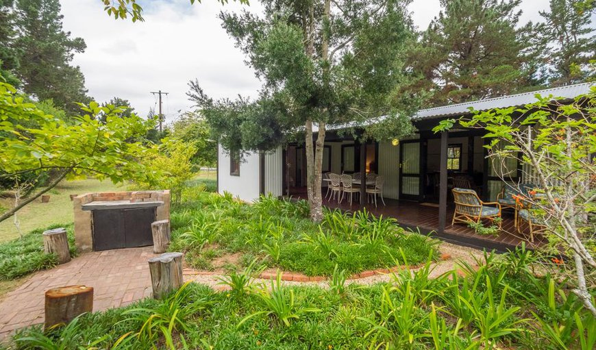 Cottage with braai area and covered deck amidst an indigenous garden.