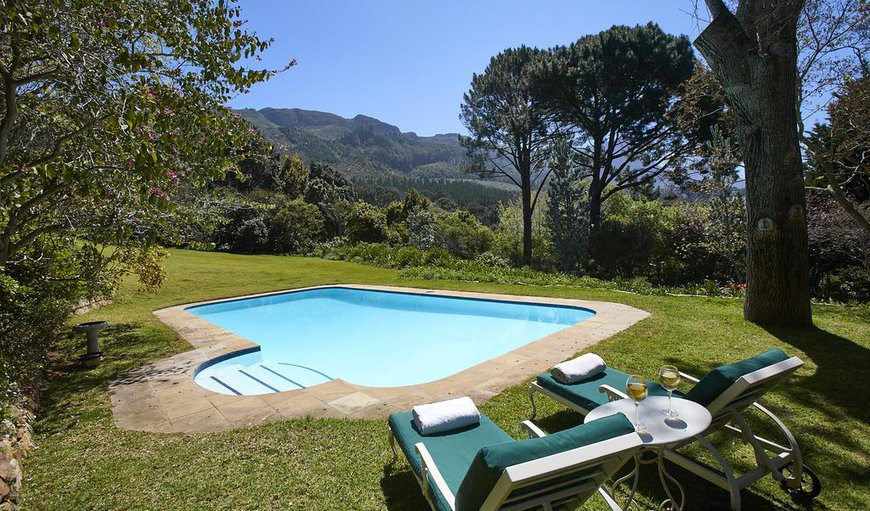 Bellevue Cottage - There is a swimming pool with lounge chairs outside.