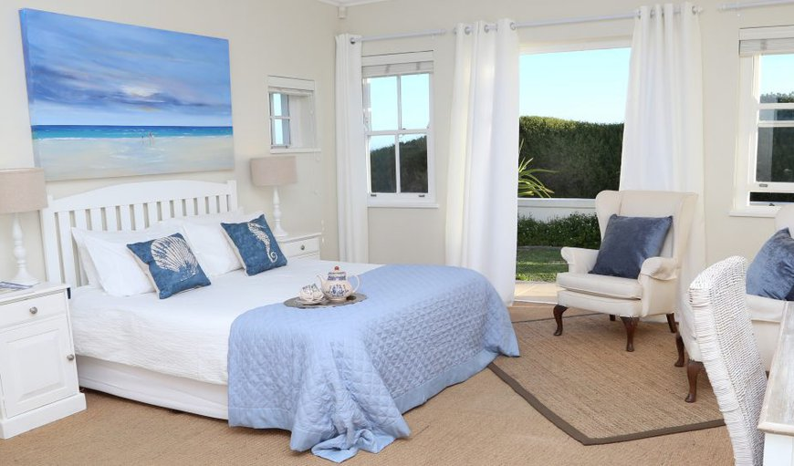 Spacious room (queen size bed) with a partial view of the ocean and double doors leading onto the front garden; wingback chairs for reading and relaxing, and a separate shower and Victorian bath in the en suite bathroom.