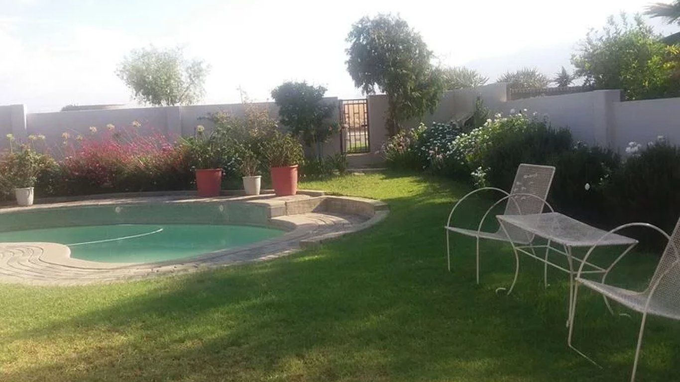 Swimming Pool Area With Garden And Mountain Views.