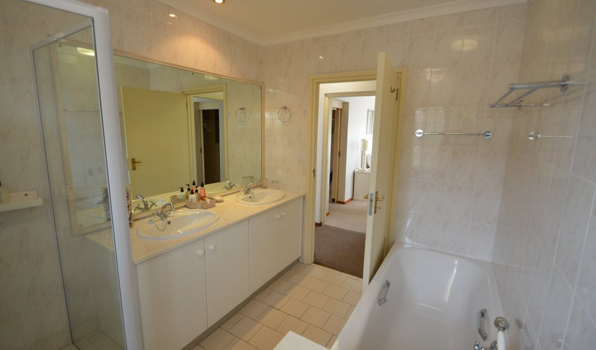 Sunkissed adjoining bathroom with shower, bath and twin basins