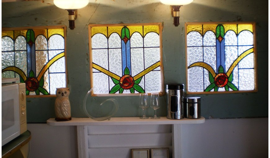 The old kitchen was made from salvaged and reclaimed material. These three beautiful stained glass windows were found in an old cellar and a window front was created with them