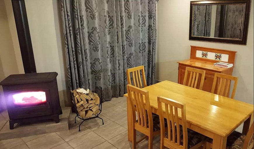 Dining room with large enclosed fireplace. Firewood is provided.