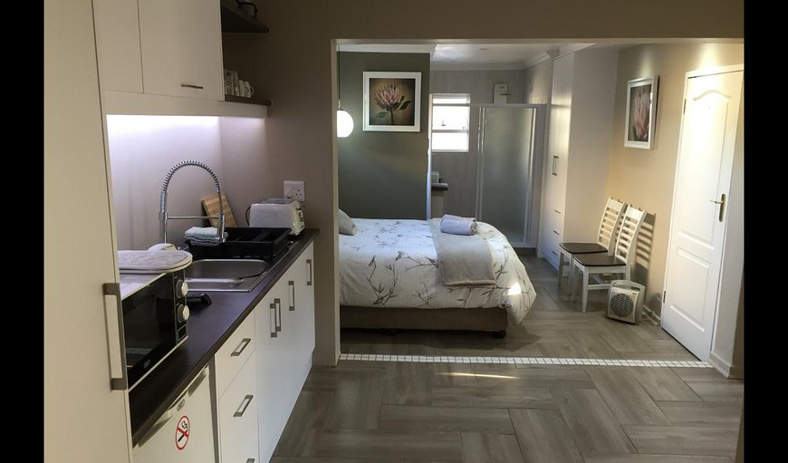 Hummingbird Suites - Protea with a kitchenette and a queen size bed.