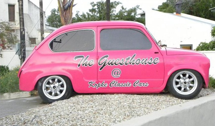 "A pink sign-written Fiat 600, nicknamed ""Pinky"" displayed on the corner of the property"
