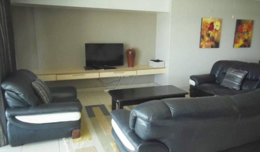 Lounge with comfortable seating and a TV with DStv