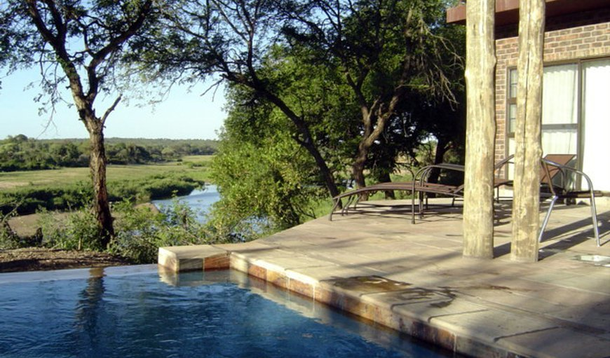 The thatch-roof house is situated on the banks of the Crocodile River, overlooking the Kruger National Park.