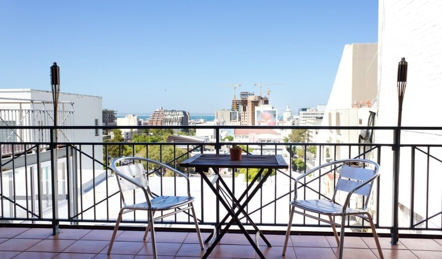 This beautiful loft apartment features a balcony with a table and two chairs overlooking Heritage Square and Table Bay.