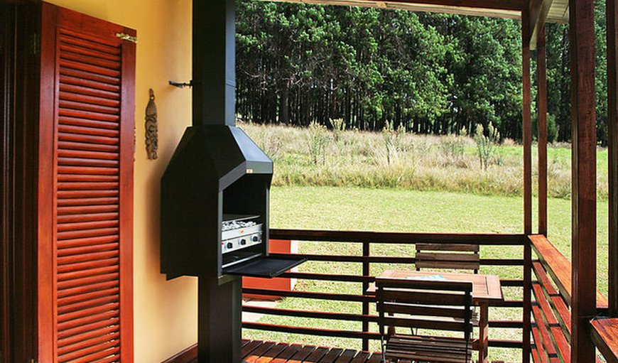 Wooden shutters open up onto a patio with braai facilities and an outdoor dining table.
