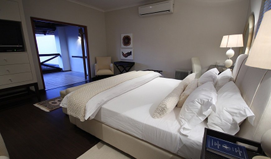 Spacious en-suite bedroom with King-size bed, lounge and private balcony access